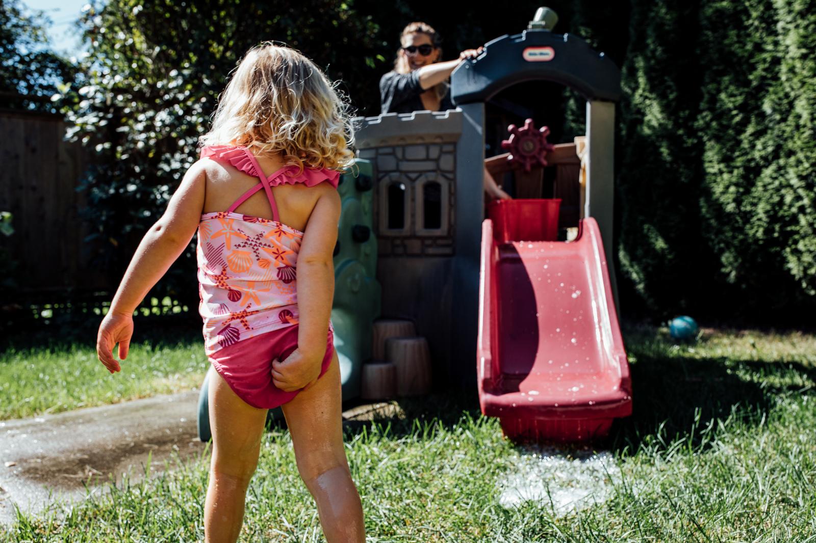 toddler pulls at bathing suit after sliding