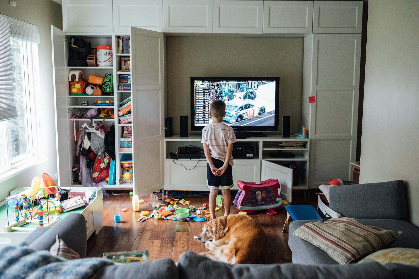 boy watches nascar race on tv in messy playroom