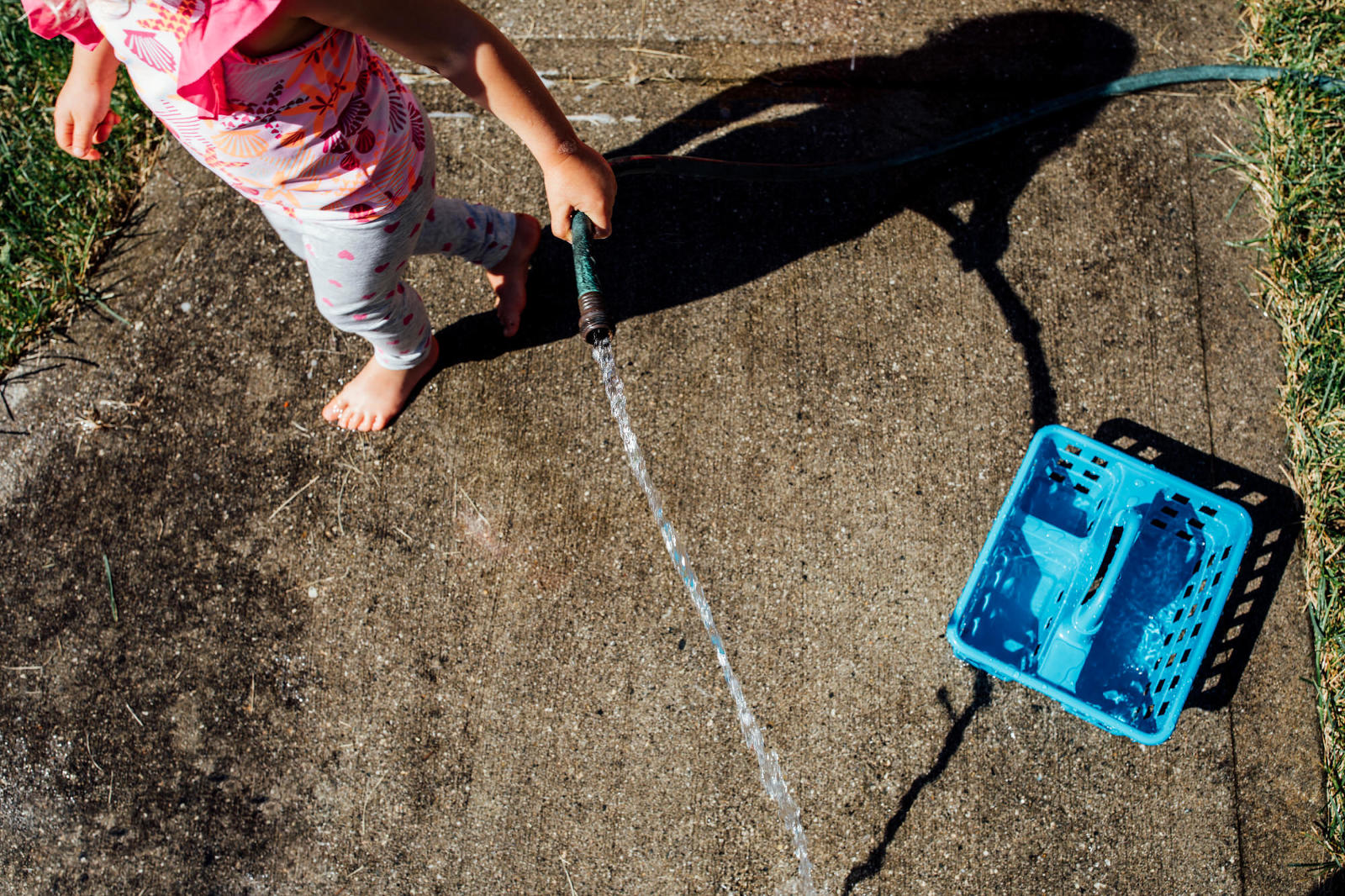 barefoot girl holds water hose in summer with shadow