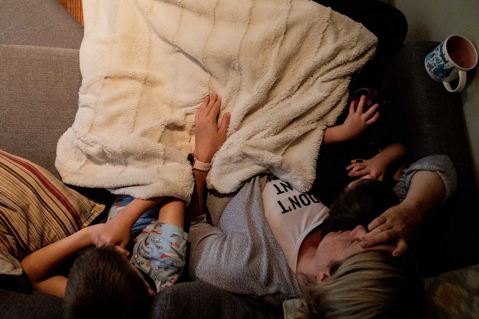 tired mom snuggles on couch with boys with her coffee